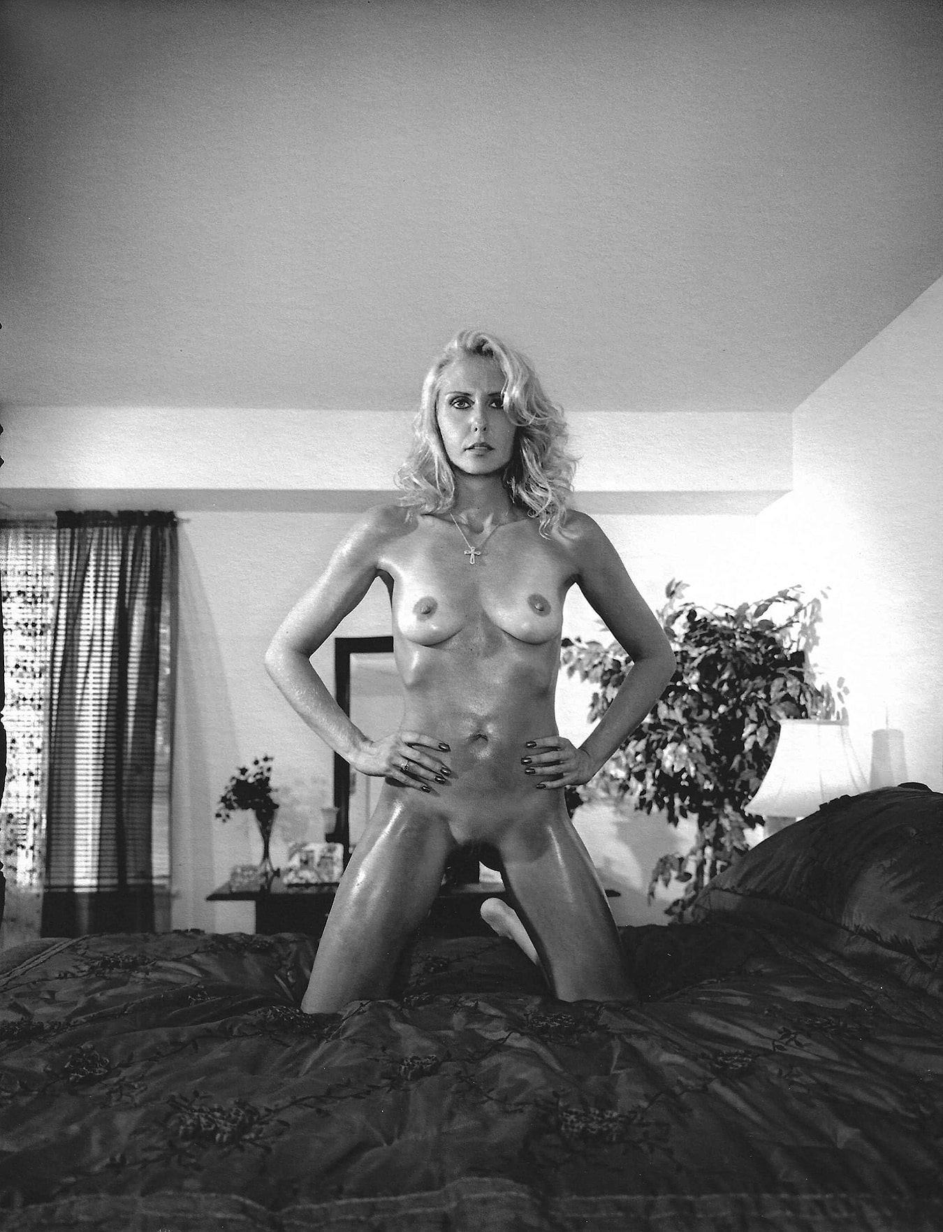Portrait of blonde woman naked on her bed